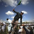 Kashmiri Muslims jump over a fence from to join a protest rally after Eid al-Fitr prayers. (AP Photo/Altaf Qadri)