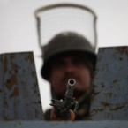 An Indian paramilitary soldier keeps vigil atop an armored vehicle during a  curfew watch. (AP Photo/Altaf Qadri)