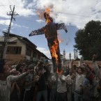 Kashmiri protesters lift and burn an effigy of US President Barack Obama. (AP Photo/Altaf Qadri)
