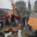 Kashmiri protesters shout slogans as they burn effigies of Indian prime minister and the Jammu and Kashmir state chief minister. (AP Photo/Altaf Qadri)