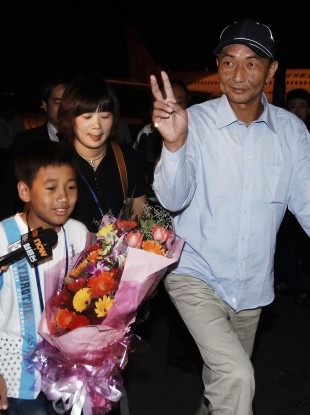 Zhan Qixiong, the Chinese trawler captain released from detention in Japan, is accompanied by his wife and son after arriving at the airport in Fuzhou