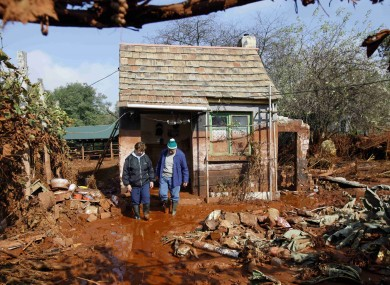 Residents inspect damage in a yard in Kolontar yesterday