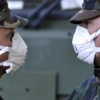 Hungarian soldiers wearing protective masks talk to each other while cleaning streets flooded by toxic red sludge in Devecser.