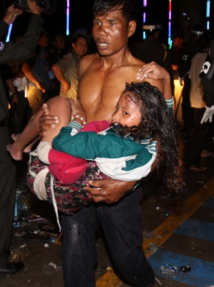 An injured Cambodian is carried by another visitor after a stampede on a bridge in Phnom Penh.