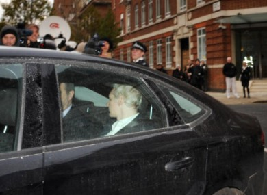 Julian Assange is driven into Westminster Magistrates Court in London yesterday.