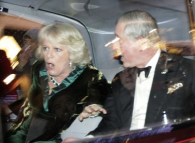 Prince Charles and Camilla react as their car comes under attack from protesters last night.