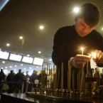 A clergyman lights candles at a site of a blast at Domodedovo airport near Moscow where a suicide bomber killed scores of people on Monday.