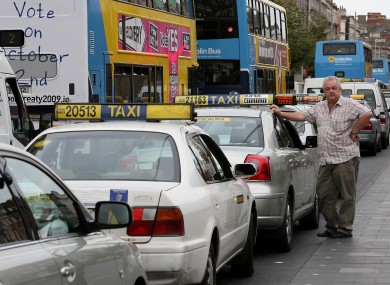 A taxi driver waits by his parked taxi on O'Connell Street, Dublin, during the protest by taxi drivers protesting over the current economic conditions in the industry in 2009.