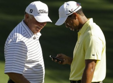 Mark O'Meara checks out something on Tiger's phone during a practice round at last year's Masters - don't ask!
