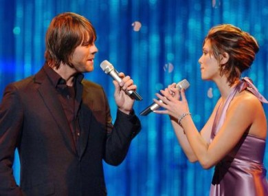 Brian McFadden and Delta Goodrem performing together.