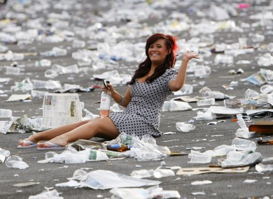 A racegoer sits amongst the rubbish after Aintree Ladies Day last year.