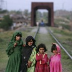 Afghan refugee girls pose for a picture while playing on a railway track, on the outskirts of Islamabad, Pakistan.