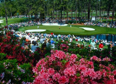 Golf fans watch practice on the par three 16th hole during a practice round of The Masters yesterday. Storms hit the Augusta area overnight.