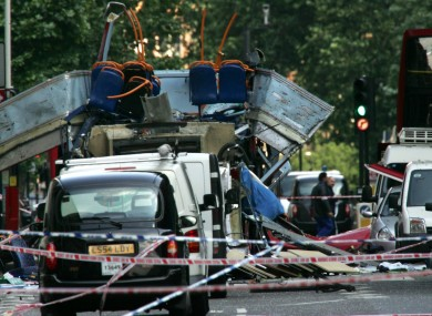 The wreckage of a double-decker bus with its top blown off and damaged cars scattered on the road at Tavistock Square in central London after the 7/7 bombings of 2005.