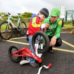 Liam Nolan, 2, from Waterford gets his bike sorted out before the stage start with some advice from race leader Gediminas Bagdonas of the An Post Sean Kelly Team.