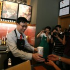 Wang Jinlong, chairman of the board of Starbucks Greater China, serves the first coffee to a customer in the first Chinese Starbucks cafe in Kunming, Yunnan province. (Long yudan/AP/Press Association Images)