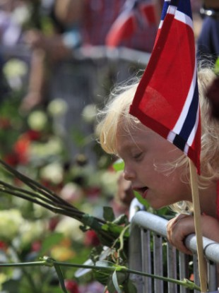 People gather around thousands of flowers and tributes laid outside the Oslo Cathedral in Oslo, in memory of the victims of July 22 bomb attack and shooting rampage.