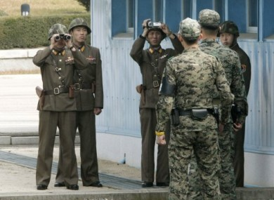 North Korean Army soldiers, background, look at the southern side as South Korean Army soldiers stand guard at the border village of Panmunjom in October 2010.
