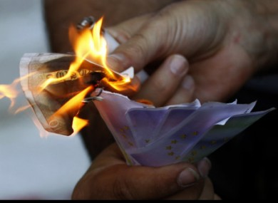 A protestor uses a burning €10 note to set fire to fake banknotes during an anti-austerity protest outside Greece's central bank in Athens today.