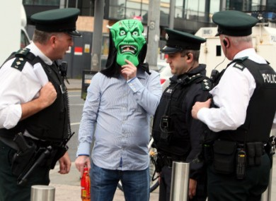 A man conceals his identity with a Halloween mask as he arrives at Belfast crown court for the so-called 'supergrass' trial today. 