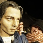 A woman poses with the bust of US actor Johnny Depp in the village of Drvengrad in south Serbia. 