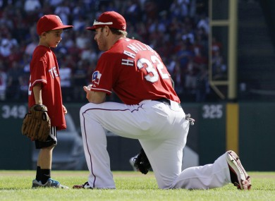 After throwing out a ceremonial first pitch, Cooper Stone, 6, talks with Texas Rangers left fielder Josh Hamilton.