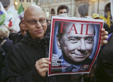 A man, waiting for the resignation of Berlusconi, shows a mock magazine cover displaying the former PM in Rome.