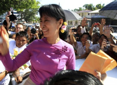 Myanmar democracy icon Aung San Suu Kyi waves her hand to supporters as she leaves the National League for Democracy party's headquarters after a meeting in Yangon, Myanmar today.