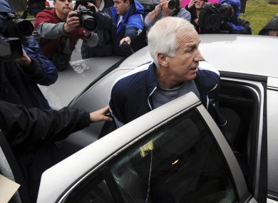 Jerry Sandusky is escorted to a police car after he left his house in handcuffs and a Penn State tracksuit.