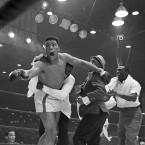 Cassius Clay's handlers hold him back as he reacts after he is announced the new heavyweight champion of the world on a seventh round technical knockout against Sonny Liston at Convention Hall in Miami Beach.