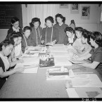 Mrs Ryie Yoshizawa and her class of women students crowd around a table, looking at fashion magazines including 'Vogue' and patterns. (Library of Congress, Prints & Photographs Division)