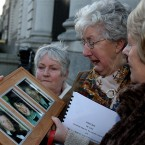 Bride McDermot (centre) holds a picture of her children George,Marcella and William as she leaves Government Buildings in Dublin after collecting a new report of the Independent Examination of the Stadust Victims Committee.