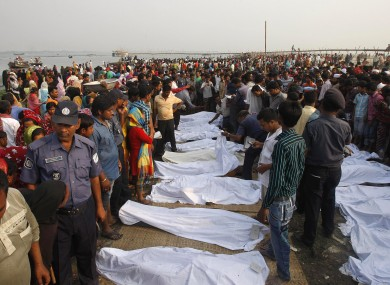 A crowd gathers around the dead bodies of victims of a ferry that capsized in the Meghna River