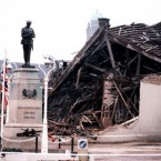 1987: The Cenotaph at Enniskillen with the devastated community centre in the background. 11 people died and more than 50 were injured in a massive IRA bomb explosion just before a Remembrance Day ceremony took place in the Co. Fermanagh town of Enniskillen. 
