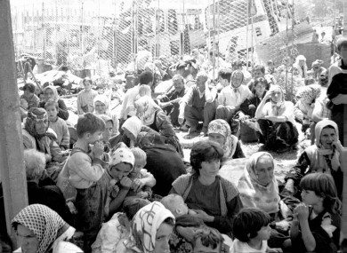 Some of the 30,000 predominantly Muslim refugees from the eastern Bosnian enclave of Srebrenica wait for transportation on 12 July 1995.
