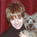 Liza Minnelli poses with her dog Lilly in her dressing room at the Opera House ahead of a benefit concert in Paris, France in 1989. (AP Photo/Lionel Cironneau/Press Association Images)
