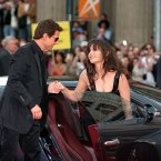 Tom Cruise helps fiancee Katie Holmes out of a Bugatti automobile in their first public appearance after the birth of their daughter Suri in 2006 (AP Photo/Branimir Kvartuc)