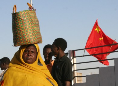 A Sudanese woman walks past a Chinese flag on a street in Khartoum