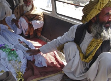 Elderly men sit with the covered bodies of three children killed the strike