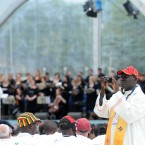 A priest, with sports cap, takes a picture of the opening ceremony.