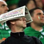 An Irish fan shelters from the rain 
