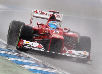 Spain's Fernando Alonso steers his car through the rain to win the qualifying of the German F1 Grand Prix in Hockenheim.