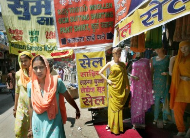 Women walk past a fabric shop at a market in Gurgaon, a suburb of New Delhi, India