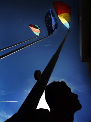Bulgarian worker looks up at Bulgarian, Romanian and EU flags Sofia in 2006