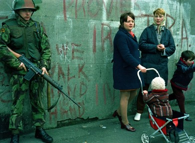 Women and children stand beside an armed British soldier in Belfast, days after Bloody Sunday in 1972
