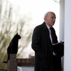 This cat is taking no chances as Liberal Democrat Treasury Spokesperson Vince Cable in the UK knocks on its owner's door in Twickenham, Middlesex.