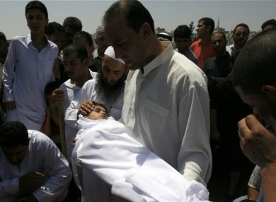A relative holds the body of 6-year-old Syrian boy Bilal El-Lababidi during his funeral in Ramtha, Jordan, Friday, July 27, 2012.