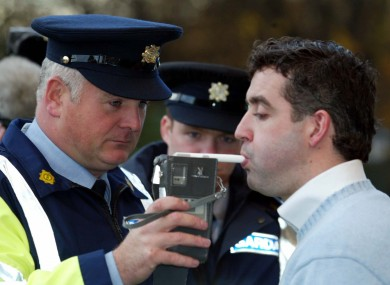 A Garda breathalises an actor during a mock driving test