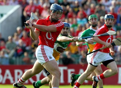 Cork attacker Patrick Horgan scores a goal while being tackled by Offaly's Conor Hernon.