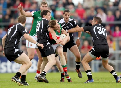 Sligo's Eugene Mullen, David Maye and Eamonn O'Hara tackle Donal Vaughan of Mayo